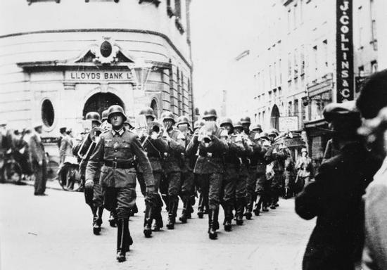 """Niemieccy żołnierze maszerują po głównej ulicy miasta St Peter Port na wyspie Guernsey. Już Już niedługo tamtejsi mieszkańcy zostaną """"wiernymi nazistami""""."""