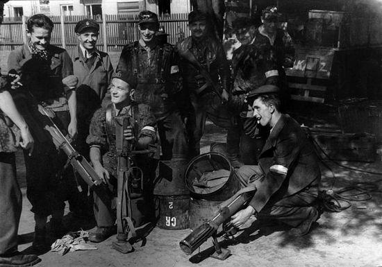 """Batalion """"Czata 49"""" był jedną z najlepiej wyszkolonych i uzbrojonych jednostek AK walczących w powstaniu. Na zdjęciu żołnierze """"Czaty"""" wyciągają z zasobników zrzutowe granatniki przeciwpancerne """"PIAT""""."""