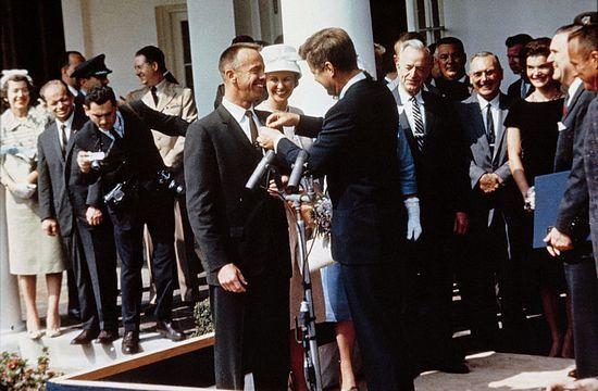 Alan Shepard dekorowany przez prezydenta Johna Fitzgeralda Kennedy'ego Medalem za Wybitną Służbę. W tle widoczne panie Shepard i Kennedy. Obie nie miały łatwego życia ze swoimi kochliwymi mężami.