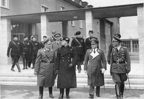 Włoski minister spraw zagranicznych Galeazzo Ciano (drugi z lewej) w Berlinie. W czasie swoich licznych wizyt w stolicy III Rzeszy Ciano był stałym bywalcem Salonu Kittty, gdzie nieświadomie wyjawiał wiele państwowych tajemnic. (źródło: Bundesarchiv, fot. Hoffmann; lic. CC-BY-SA)