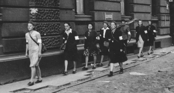 Sukienki, spódnice, bluzeczki z białym kołnierzykiem, do tego opaska na ramię. Na zdjęciu wymarsz patrolu sanitarnego Wojskowej Służby Kobiet AK na ulicy Moniuszki 9, dnia 5 sierpnia 1944 .