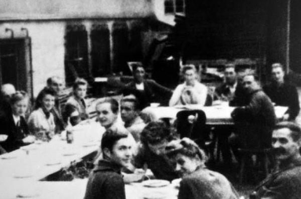"""15 sierpnia 1944 roku jeszcze było co jeść. Powstańcy ze zgrupowania """"Żywiciel"""" siedzą przy zastawionym stole na terenie gimnazjum """"Poniatówka"""" na Żoliborzu."""