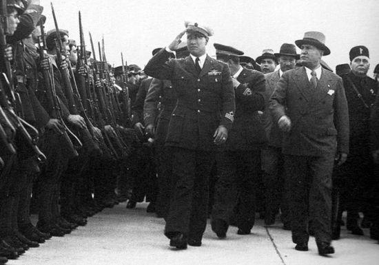 Galeazzo Ciano w mundurze pilota (salutuje) wraz z Benito Mussolinim przeprowadzają inspekcję żołnierzy wyruszających na wojnę z Abisynią. Maj 1936.